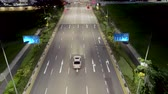 Singapore - 25 September 2018: Top View of street with intersection road and people crossing the street at night. Shot. Aerial view of city crossroad with cars and people on zebra crossing during night. Стоковые видеозаписи