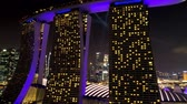 Singapore - 25 September 2018: Marina Bay Sands hotel in Singapore lighted by beautiful purple illumination and laser show at night. Shot. Moving towards the stunning Marina Bay sands at night with purple glowing.