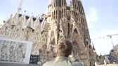 den : Spain - Barcelona, 12 August 2018: Man in leather jacket and black sun glasses taking photo of the gothic cathedral facade in a sunny day. Stock. Young tourist takes a picture of gothic style cathedral over blue sky background.