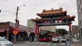 northwest : Seattle historic Chinatown Gate on an overcast day with traffic and onlookers