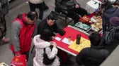 XIAN CHINA - FEB 06 2012: Fortuneteller tell fortunes for a girl in market
