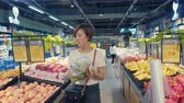 販売の : Xian, Shaanxi, China, JUNE 13, 2019. Woman shopping in a supermarket 動画素材