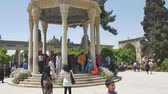 versão : SHIRAZ, IRAN - MAY 2, 2015: Visitors take a tour of the tomb of Persian poet Hafez. Dome-like structure was erected in Shiraz near his grave at Golgast-e Mosalla in 1452