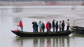 chegar : Mongla, Bangladesh, February 17, 2014 - Tourists arrive to muddy bank of one of the channels of Sundarbans National park. The Sundarbans mangrove forest is a UNESCO World Heritage Site.