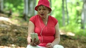 headpiece : Senior woman in red hat sits on a fallen tree in forest and communicates via smartphone