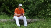 headpiece : Adult man in orange t-shirt with red smartphone sits on a fallen tree in the forest