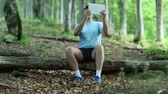 headpiece : Adult man in blue t-shirt with Tablet PC sits on a fallen tree in the forest. Man records videos on his tablet computer
