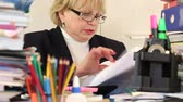 assessor : Blonde woman chief financial officer in glasses and with commercial papers sits at the table. Trouble at work. Bookkeeper with commercial papers Stock Footage