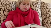 rozsáhlý : Blonde woman sitting on a couch flipping through the pages of a big book
