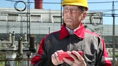 toiler : Maintenance worker with red smartphone at power station. Power engineering specialist with red smartphone at heat station. Worker in yellow hard hat at heat station. Factory worker with red smartphone