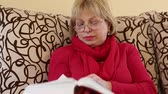 rozsáhlý : Blonde woman sits on a couch and flips through the pages of big book