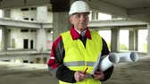 toiler : Master builder at project site. Chief architect in white hard hat, protective goggles and building drawings at construction site. Builder looks at the camera. Worker with design drawings Stock Footage