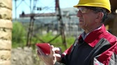 toiler : Emergency repairman with red smartphone at power station. Power engineering specialist with smartphone at heat station. Worker in yellow hard hat at heat station. Factory worker with red smartphone Stock Footage