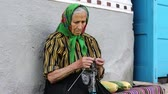 starość : Elderly woman sits on bench and knits socks. Old woman in green headscarf sits on bench near his house and knits sock. Ukrainian old woman is engaged in knitting. Female in kerchief knits woollen sock Wideo