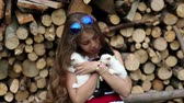 tomcat : Attractive girl holds in hands three little kittens. Beautiful girl in blue sunglasses holds in hands two white and one black cats. Girl with kittens near stack of firewood