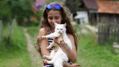 tomcat : Beautiful girl holds in hands white cat and looks at the camera. Girl in blue sunglasses holds in hands white cat. Unique cat has one blue eye and one yellow eye, it is seen in high resolution video