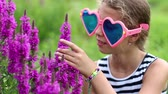 stink : Girl in big sunglasses smells flowers. Beautiful girl in big glasses in the shape of hearts near purple flowers. Flower - Epilobium angustifolium or willowweed, fireweed, sally-bloom, blooming sally