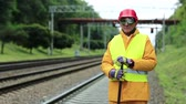 fixer : Railway worker in yellow uniform with crowbar in hands stands near railway line. Railway man in red hard hat stands near railway tracks and looks at camera. Workman with metal crowbar on railway track Stock Footage