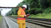 fixer : Railway worker in yellow uniform with documents. Inspector of railway traffic. Railway employee in yellow uniform on railway line. Inspector of railway traffic makes notes in his documents Stock Footage