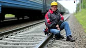 toiler : Railway worker sits on railway line. Train rides on the railroad. Railwayman in yellow hard hat sits on rail and looks at the camera. Workman on railway track