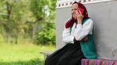 starość : Senior woman sits on bench and talks on mobile phone. Old woman sits on bench near his house and speaks on cell phone. Ukrainian old woman with red smartphone. Female with smartphone. Roar of laughter Wideo