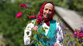 starość : Old woman stands in flowers near his house and looks at the camera. Ukrainian elderly woman in red headscarf stands near wooden hut and looks at the camera. Female looks at the camera and smiles