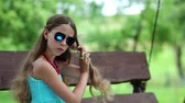 incelik : Beautiful girl braids his long hair. Attractive girl in blue sundress sits on the bench and braids his long hair. Weave braids for long hair. Pretty brunette sits on swing bench and braids his hair Stok Video