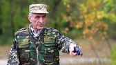 harcias : Senior man in military uniform shoots a revolver. Man with black gun. Retired officer at shooting range. Senior man in military uniform shoots a pistol in forest Stock mozgókép