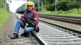 plodder : Railway worker sits on railway line. Train rides on the railroad. Railwayman in yellow hard hat sits on rail and looks at the camera. Workman on railway track