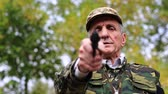 harcias : Man with gun. Man with black revolver in hand looks at the camera. Retired officer in military uniform at shooting range. Man holds in hands black revolver Stock mozgókép
