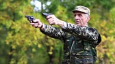 harcias : Soldier in military uniform shoots a revolver. Retired officer at shooting range. Soldier in military uniform shoots from two pneumatic handguns. Senior man shoots a two pistols in forest Stock mozgókép