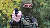 harcias : Man with gun. Man in military uniform and mask with black revolver in hand. Soldier in military uniform aims at a target. Retired officer at shooting range. Senior man in military uniform in forest Stock mozgókép