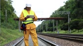 fixer : Inspector of railway traffic makes notes in tablet computer. Railway employee in yellow uniform on railway line. Railway worker in yellow uniform and white hard hat with tablet pc in hands Stock Footage
