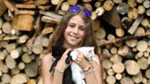 tomcat : Beautiful girl in blue sunglasses holds in hands white and black cats. Attractive girl holds in hands two little kittens. Girl with kittens near stack of firewood