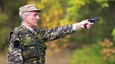 harcias : Man with black gun. Senior man in military uniform shoots a revolver. Retired officer at shooting range. Senior man in military uniform shoots a pistol in forest