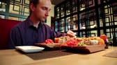 diet : Man eats sushi in japanese restaurant. Man sits at the table in restaurant and eats japanese food Stock Footage