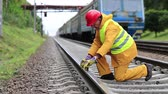 plodder : Railway man in red hard hat sits on railway tracks and looks at the train. Workman with level measuring instrument. Railway worker in yellow uniform with level measuring instrument on railway line Stock Footage