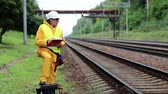 toiler : Inspector of railway traffic makes notes in his documents. Railway employee in yellow uniform on railway line. Railway worker in yellow uniform and white hard hat with documents in hands