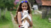 cattish : Girl in blue sunglasses holds in hands white cat. Pretty girl holds in hands white cat and looks at the camera. Unique cat has one blue eye and one yellow eye, it is seen in high resolution video