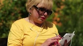headpiece : Senior woman in yellow shirt with cigarette sits on the bench and uses white smartphone Stock Footage
