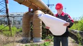 toiler : Worker in red hard hat with engineering drawing near heating main pipeline at heat electric power station. Maintenance engineer with project drawing at heat electric power station Stock Footage
