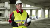 whatman : Chief architect at construction site. Chief architect in white hard hat and protective goggles at construction site looking at the camera Stock Footage