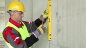 toiler : Builder in yellow hard hat with level at project site. Worker in yellow hard hat with level at building site