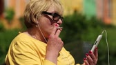 headpiece : Senior woman in yellow shirt with cigarette sits on the bench and communicates via smartphone