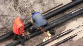 insulated : Workers in pipeline trench reconstruct hot water supply system by new technology