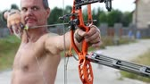 bowman : UKRAINE, KIEV REGION, KOPACHIV VILLAGE, AUGUST 14,2016: Archer shoots a bow at a target. Man training at archery with bow and arrow. Man holds bow in his left hand