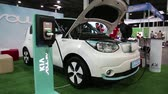 kia : UKRAINE, KIEV, JUNE 10, 2016: People at exhibition of electric cars. White KIA Soul EV electromobile is being charged. Car with openned bonnet