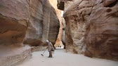 siq : JORDAN, PETRA, DECEMBER 5, 2016: Cleaner in Siq - a narrow passage, gorge that leads to the ancient city of Petra, originally known to Nabataeans as Raqmu - historical and archaeological city in Jordan