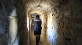 Woman goes inside stone fortress, Kamianets-Podilskyi city, western Ukraine Stock Footage