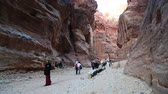 siq : JORDAN, PETRA, DECEMBER 5, 2016: People in Siq - a narrow passage, gorge that leads to the ancient city of Petra, originally known to Nabataeans as Raqmu - historical and archaeological city in Jordan